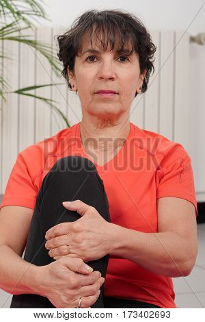 Middle-aged woman doing fitness exercises at home
