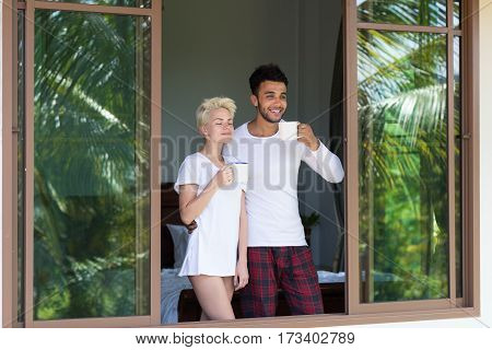 Young Couple Drink Coffee Or Tea, Man And Woman Awake Enjoy Tropical Forest View From Bedroom Hotel Room