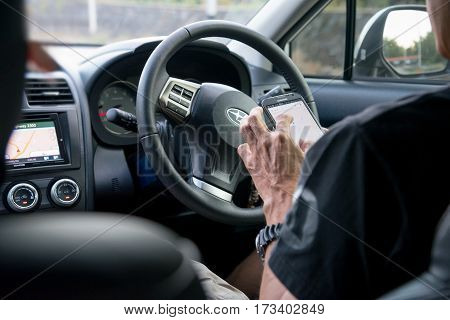 Lopburi province Thailand - January 14 2017 : Asian man stop driving and using a smartphone. Car driver use gps mobile app for traveling. Focus on hand holding cellphone.