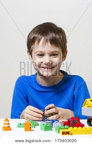 Happy kid playing with colorful plastic construction toy blocks at the table. Children education toys leisure concept