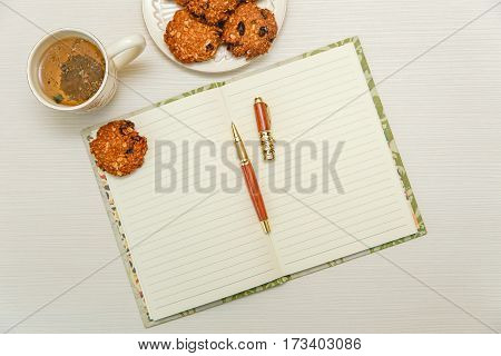 open note book with tea,cookies.brown pen.white wooden table.