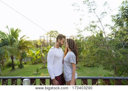 Young Couple On Terrace Tropical Hotel, Man And Woman In Love Tropic Holiday Vacation Honeymoon Green Forest Lanscape