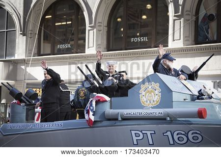NEW YORK - NOV 11, 2016: Vets wave from the Navy Club of the USA, Lancaster, PA., Ship No. 166 parade vehicle during the 2016 America's Parade on Veterans Day in New York City on November 11, 2016.