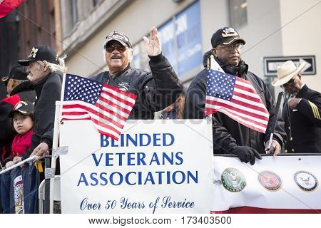 NEW YORK - 11 NOV 2016: Vets ride on the Blinded Veterans Association parade float in the annual Americas Parade up 5th Avenue on Veterans Day in Manhattan.