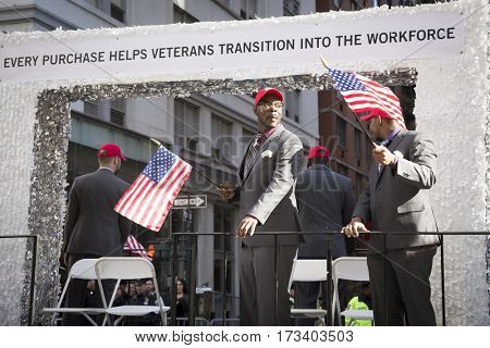 NEW YORK - 11 NOV 2016: US vets wave American Flags as they stand on a parade float in the annual Americas Parade up 5th Avenue on Veterans Day in Manhattan.