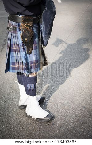 NEW YORK - 11 NOV 2016: Bagpiper from a pipes and drums band wearing a blue plaid kilt marches in the annual Americas Parade up 5th Avenue on Veterans Day in Manhattan.