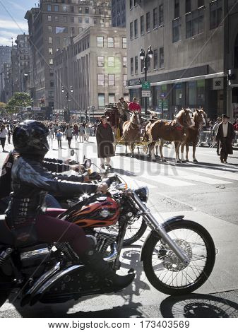 NEW YORK - 11 NOV 2016: Motorcycle riders wait for the Wells Fargo horsedrawn carriage to pass at the annual Americas Parade on 5th Avenue on Veterans Day in Manhattan.