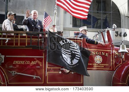 NEW YORK - 11 NOV 2016: Vets, members of the New York Fire Department, FDNY, ride on a fire truck during the annual Americas Parade up 5th Avenue on Veterans Day in Manhattan.