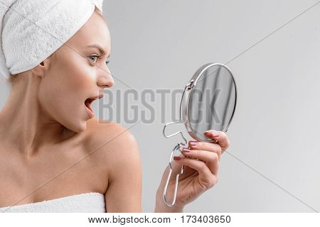 What a pretty face. Excited young girl is posing in front of mirror. She is standing wrapped by white towel. Isolated and copy space in right side