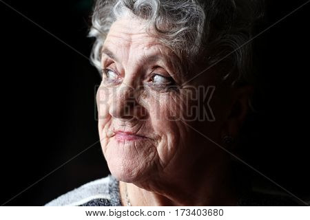 Grandmother looking on a black background. Old woman