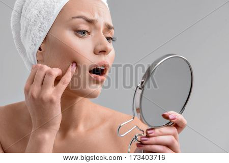 Pimple again. Sad young girl is touching her face and looking at mirror with shock. She is standing with towel over her hair. Isolated