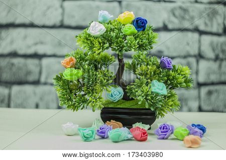 Decorative tree against the background of a brick wall