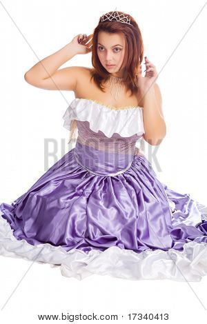 young attractive sitting woman in long lilac-coloured ball dress and with diadem on head isolated on white background