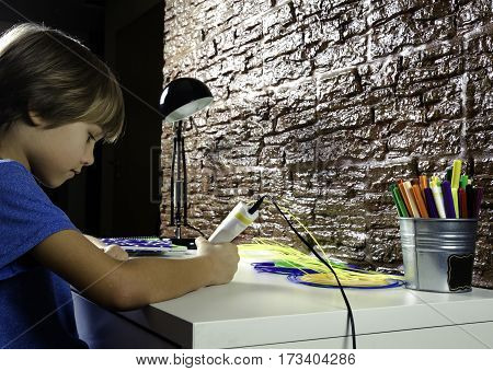 Happy child creating with 3D printing pen at home. Boy making new item. Creative technology leisure education concept