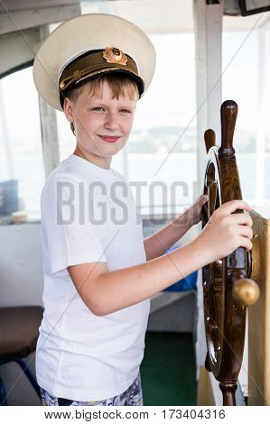 Boy with captain cap holding the steering wheel of the ship