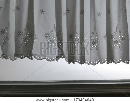 Silhouette white Lace satin curtain hanging on window above window jamp with sunlight semitransparent behind decoration interior room photo
