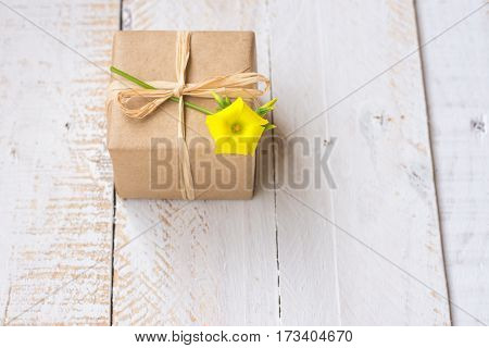 Gift box wrapped in craft paper tied with twine spring yellow flower white plank wood background minimalistic copyspace kinfolk top view