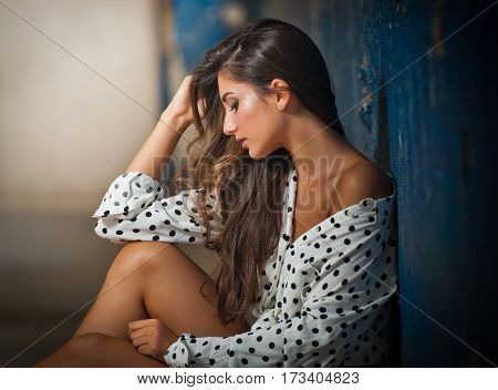 Beautiful girl with unbuttoned shirt posing, old wall with peeling blue paint on background. Pretty brunette sitting on the floor. Attractive dark long hair young woman with sensual expression on face