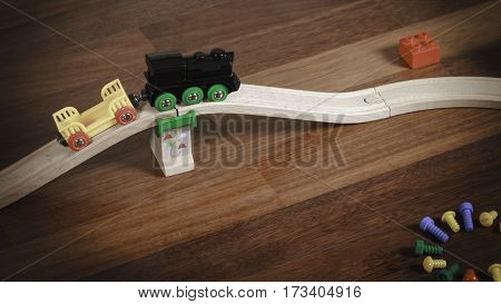 Toy train and wooden rails with bridge and colorful toys around. Top view