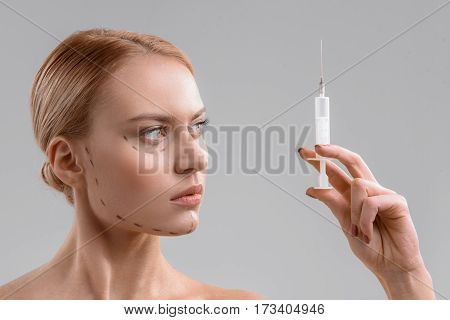 I am ready for operation. Confident young woman is holding syringe with rejuvenation liquid. She has correction lines on her face. Isolated