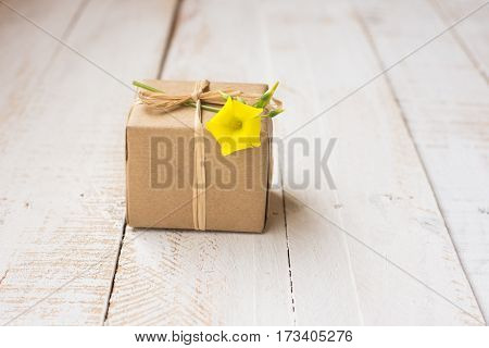 Gift box wrapped in craft paper tied with twine spring yellow flower white plank wood background minimalistic copyspace kinfolk