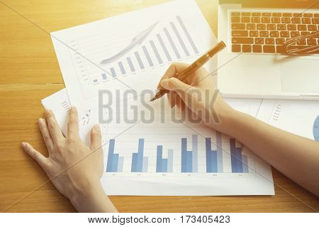 Photo of human hands holding pen and marking graphs monitoring in documents