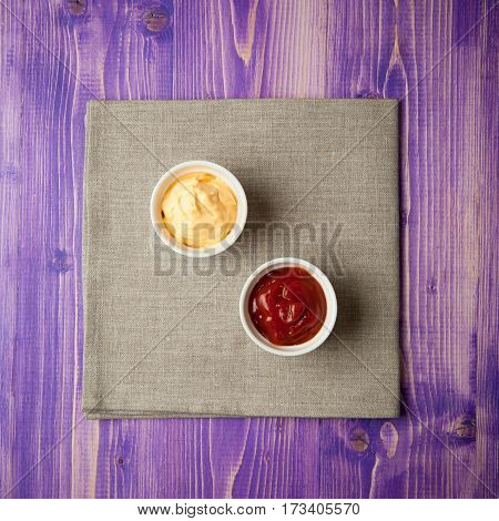 white cups with ketchup and cheese on gray napkin made from canvas on purple wooden table