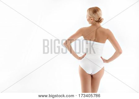 Sexy girl is posing with arms akimbo in slinky lingerie. She is showing her back boastfully. Isolated and copy space in left side