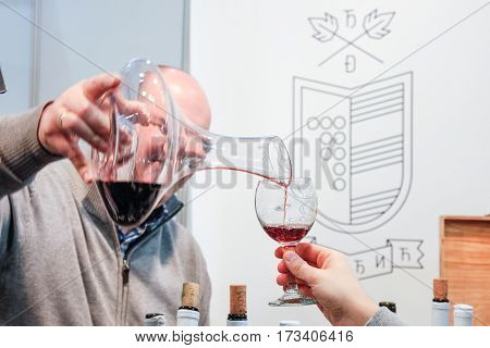 BELGRADE SERBIA - FEBRUARY 25 2017: Red wine being poured into a glass for a wine tasting during the 2017 Belgrade Tourism Fair