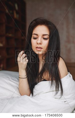 Sensual woman with dark hair sitting on a bed at home