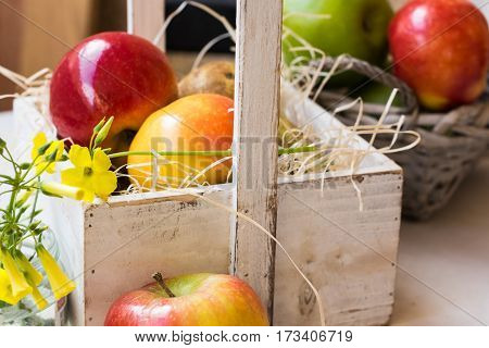 Vintage wood box in Provence style with red yellow apples pears on straw basket with fruits spring flower table outdoors in garden harvest