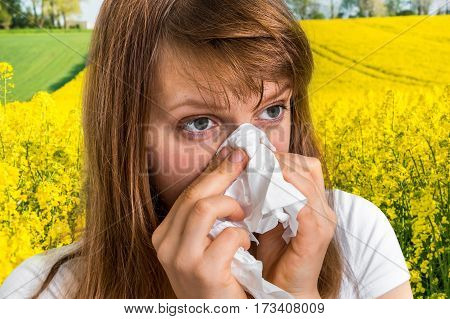 Woman with allergy on yellow rape field sneezing in tissue - blooming rapeseed field and allergy
