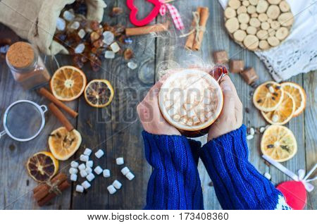 cup of hot chocolate with marshmallows in human hands top view