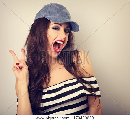 Crazy Young Female Model In Blue Hat Showing Rock Gesture With Wide Opened Mouth. Bright Makeup And
