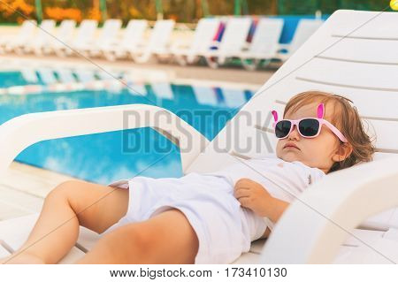 Endless summer Cute baby relaxing at sunbed near pool at resort. A little girl wearing sunglasses. Fashion child burn