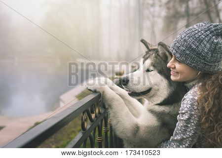 Image of young girl with her dog, alaskan malamute, outdoor at autumn or winter. Domestic pet. Husky