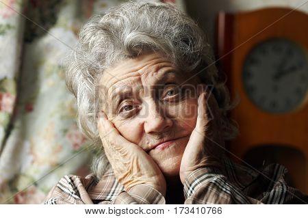 Sad grandmother portrait with hands on a dark background
