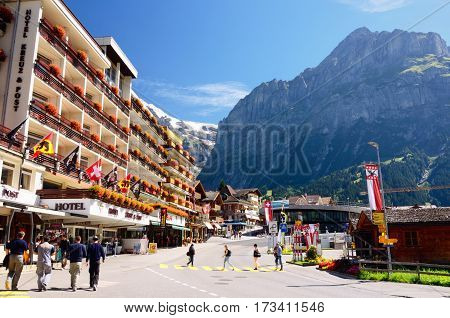 GRINDELWALD, SWITZERLAND - AUGUST 28, 2014: Hotel Kreuz & Post; Mountains in the Background on August 28, 2014 in Grindelwald, Switzerland. Grindelwald is a Mountain Ski Resort Village in Jungfrau Region, Switzerland.