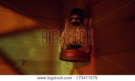 Ancient lamp on a wooden wall. Reflection of stained-glass window. Close up