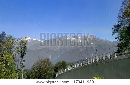 Well-maintained road with fencing and lighting is among high mountains covered with forest.