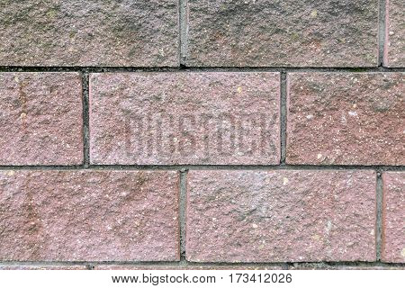 Fragment of brick walls painted in pink and held together with cement mortar. Presents closeup. Background image.