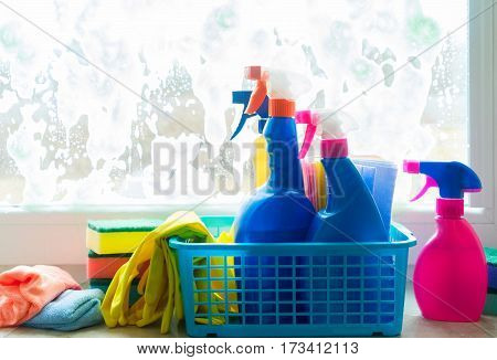 Spring cleaning - container with sprays, gloves and rubbers on windowsill