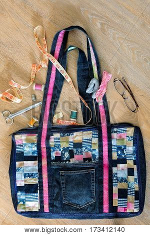Beautiful female bag of colorful scraps of fabric in patchwork. Handmade. Next are the threads needles scissors inch.