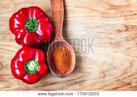 red ripe sweet bulgarian bell peppers and paprika powder in the spoon on wood background