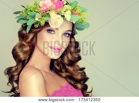 Beautiful woman model brunette with long curly hair floral wreath on the head . Spring girl . Summer fresh image .