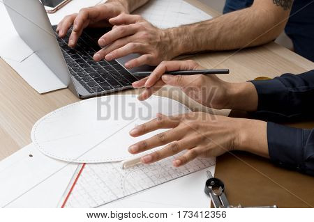Coworkers working on a new project, wooden desk with plans and laptop