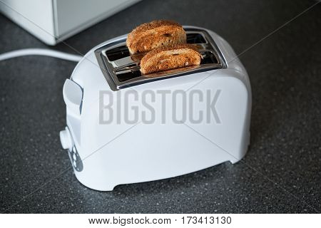 A toaster with slices of bread in the kitchen