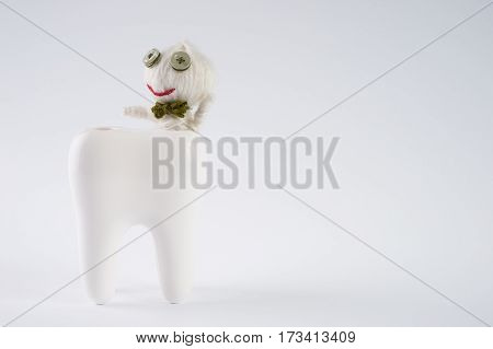 Tooth with cute dolls attacked by bacteria on isolate white background with copy space. Dental caries concept