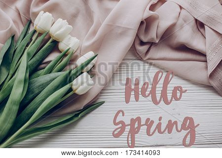 Hello Spring Text Fresh Sign. Stylish White Tulips On Beige Soft Fabric And Rustic Wooden Table Back