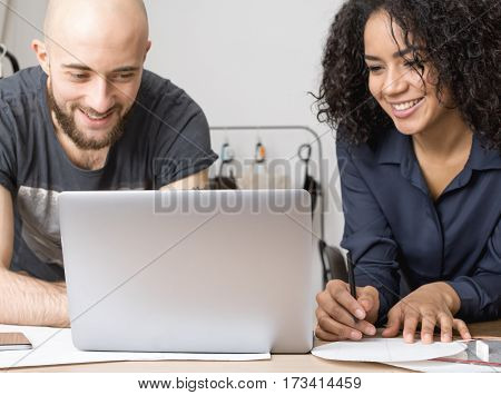 Two young business people smiling. Looking on the laptop monitor.